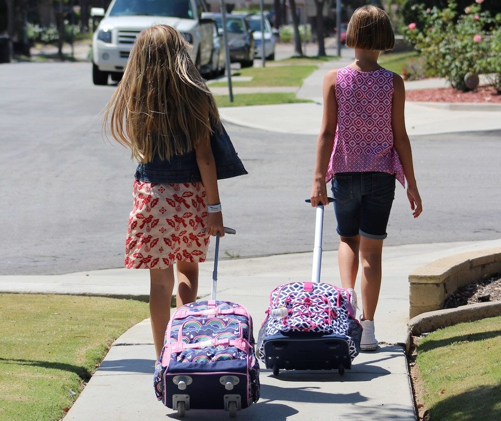 Nichole and Dianna walking to school with their rolling backpacks.