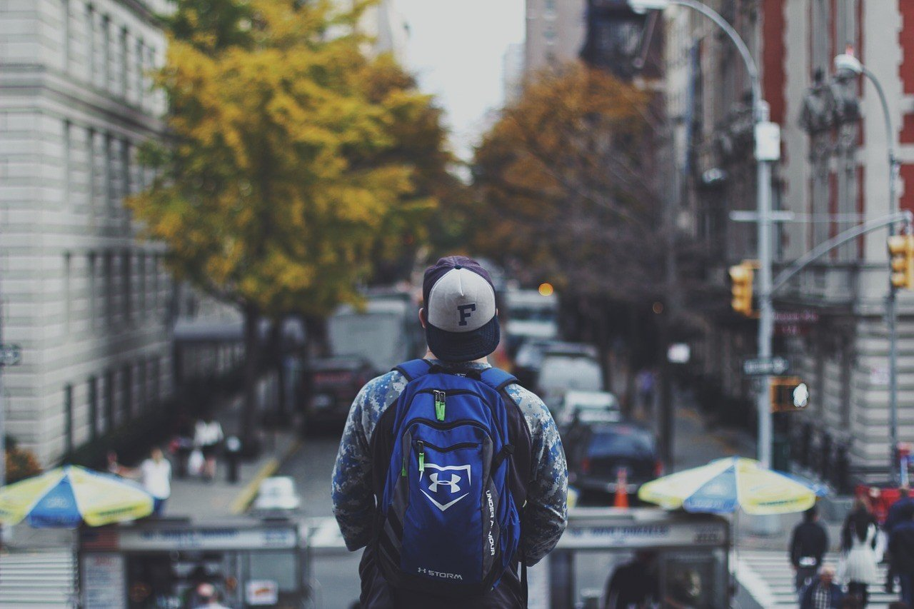 boy overlooking the city with backpack