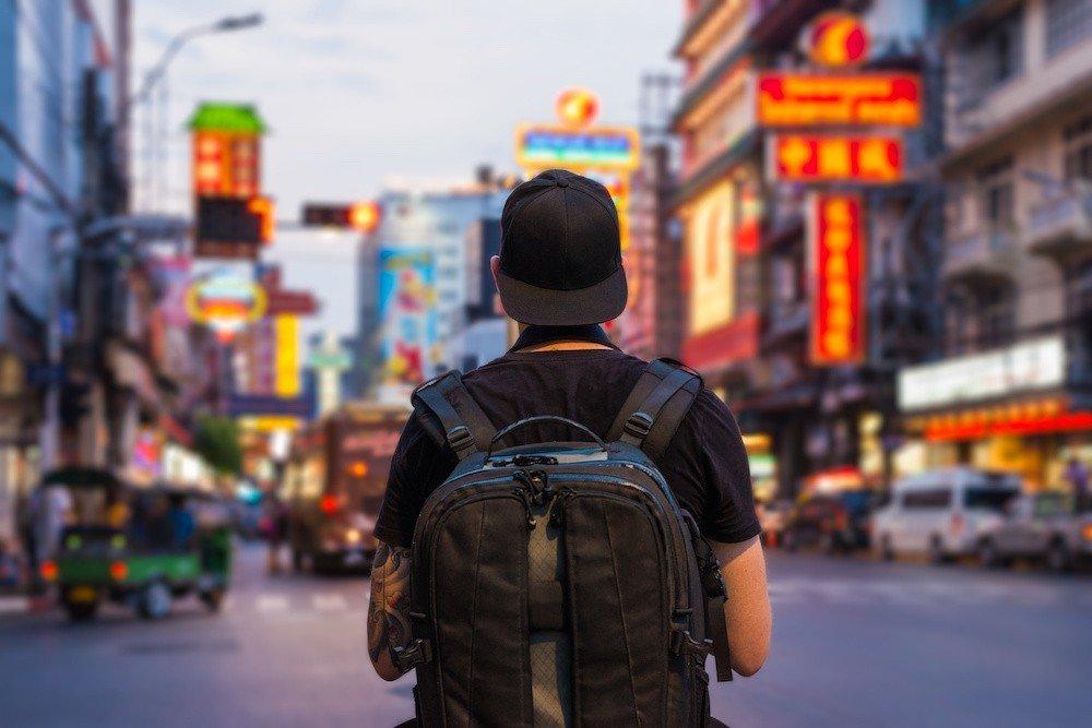man wearing backpack in bangkok city